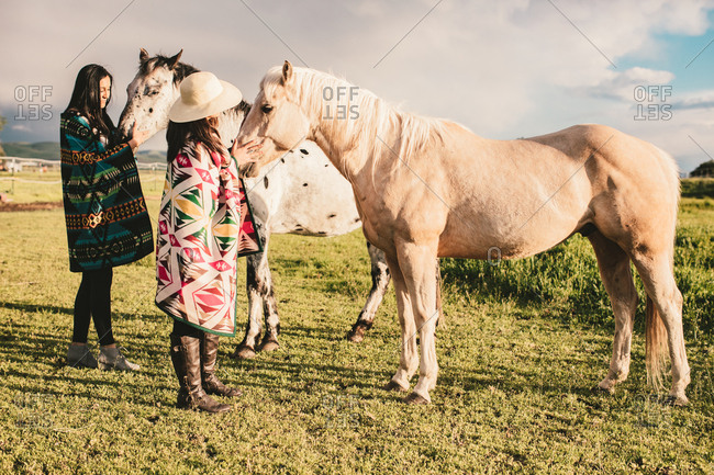 Two woman with their horses in field