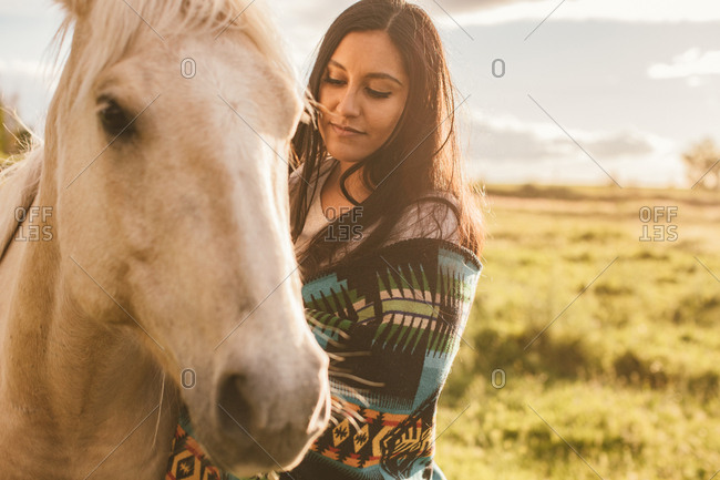 Woman with her palomino horse at dusk