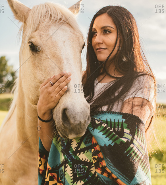 Portrait of woman with her affectionate palomino horse