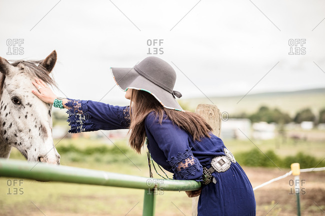Woman leaning over fence to pet a spotted horse