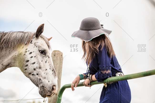 Spotted horse approaching woman standing at fence