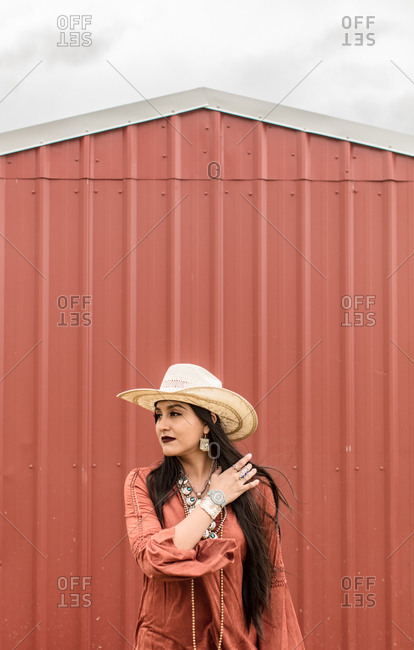 Woman in western hat standing by barn