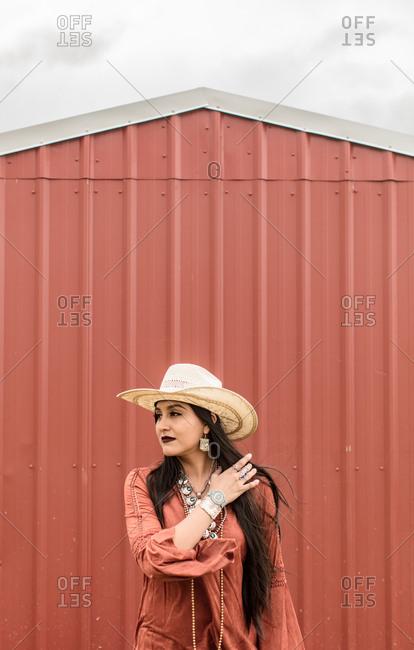 Woman in western hat standing by barn