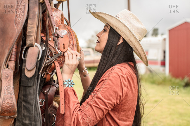 Woman in straw cowboy hat looking at saddles