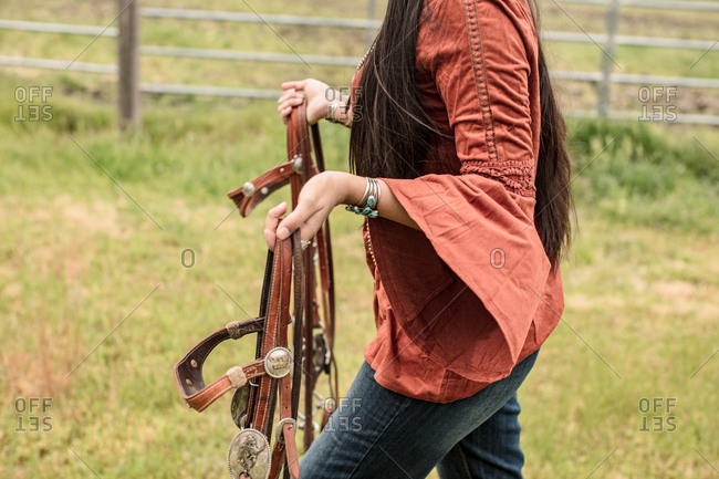 Woman carrying leather reins