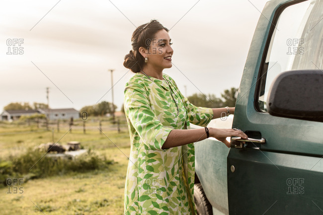 Woman in a vintage style dress and jacket getting into truck
