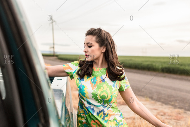 Woman in flowered dress at back of pick-up truck