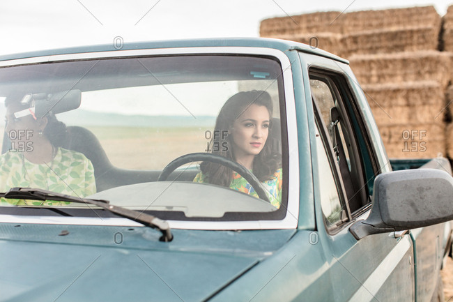 Two sisters in pick-up truck in hay field