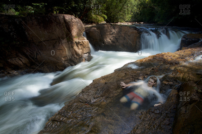 A boy relaxes in a natural pool next to a waterfall on the upper Siduk River.
