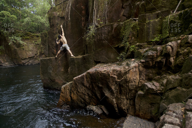 A man doing deep water free soloing on the cliffs in the gorge below Riam Parit, or the Channel Falls, an unusual slot waterfall on the upper Siduk River.