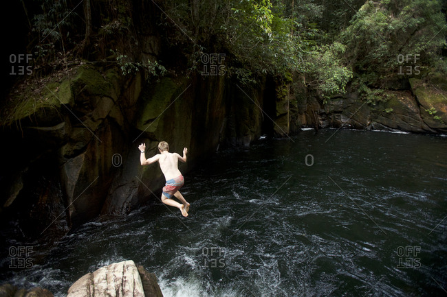 A boy plunges into the deep dark pool beneath Riam Parit, or the Channel Falls, an unusual slot waterfall on the upper Siduk River.