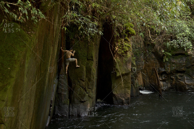 Gunung Palung National Park, Indonesia - August 17, 2016: A man doing deep water free soloing on the cliffs in the gorge below Riam Parit, or the Channel Falls, an unusual slot waterfall on the upper Siduk River.