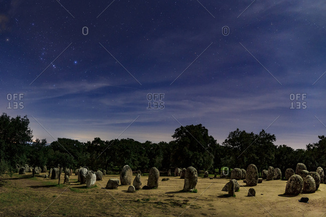 Almendres Cromlech standing stones and Orion in the night sky.