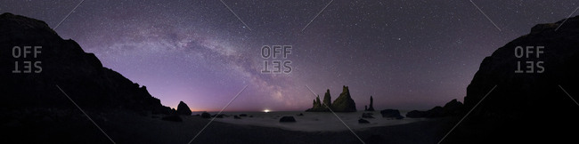 Panoramic view of the Milky Way over the basalt sea stacks known as Reynisdrangar in Vik, Iceland.