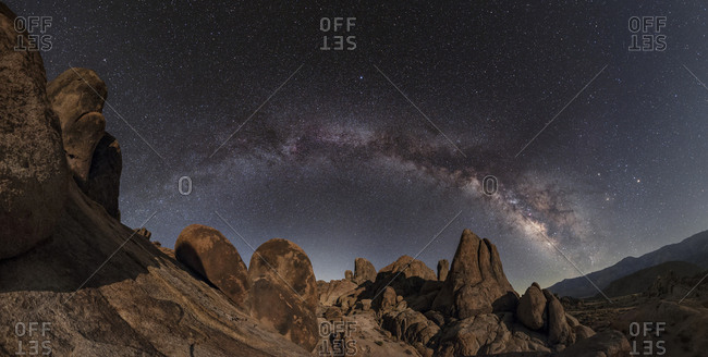 Panoramic view of Milky Way over rock formations in California.