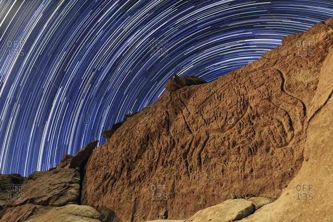 Time-exposure of star trails above ancient petroglyph of llamas in Rainbow Valley, Chile.