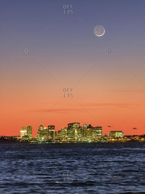 The new moon in a vibrant dusk above Boston skyline and the Atlantic Ocean.