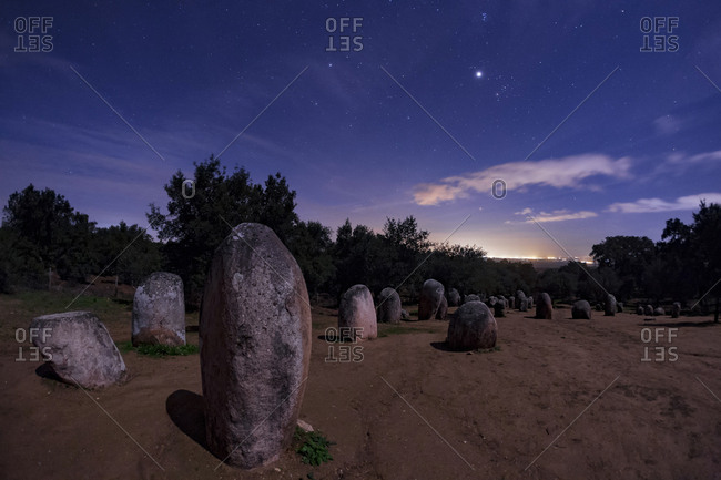 Almendres Cromlech standing stones with Jupiter and Pleiades in the night sky.