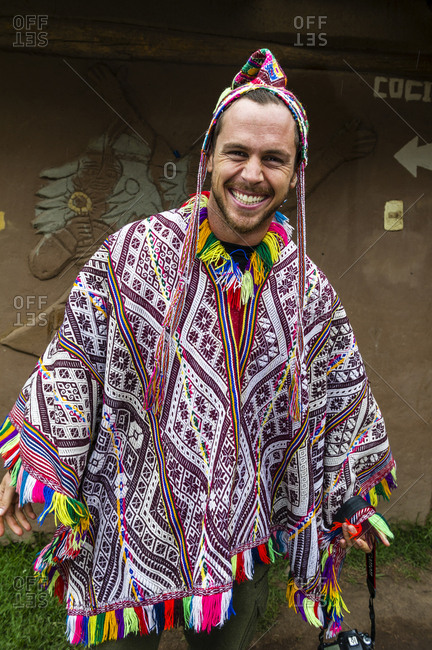 A tourist from the United States wearing a colorful poncho and chullo woven hat.