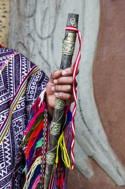 An Amaru man wearing a colorful handwoven poncho holding a brass and timber flute.