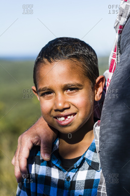An Aboriginal boy cradled in his father's arms.
