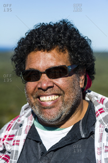 A smiling Aboriginal man wearing sunglasses on a bright sunny day.