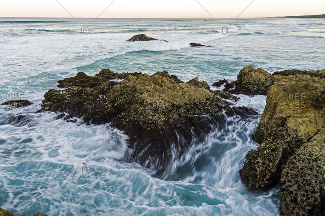 Waves smash against jagged rocks on a pristine coastline.