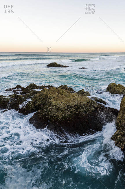 Waves smash against jagged rocks on a pristine coastline.