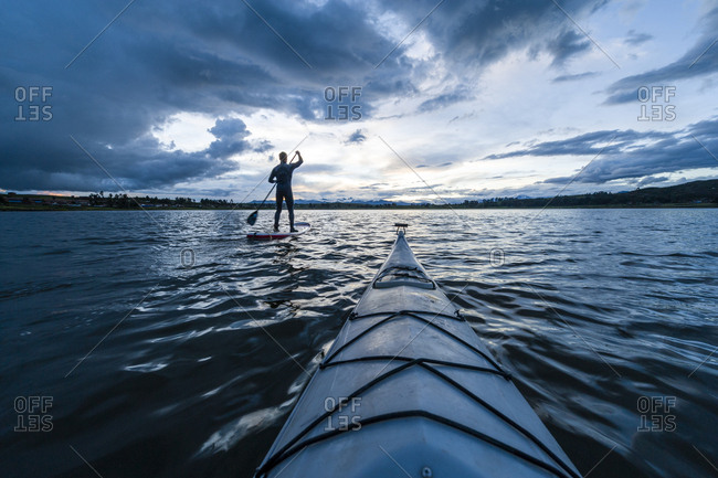 A canoe bow on a still lake and a man on a paddleboard beneath storm clouds.