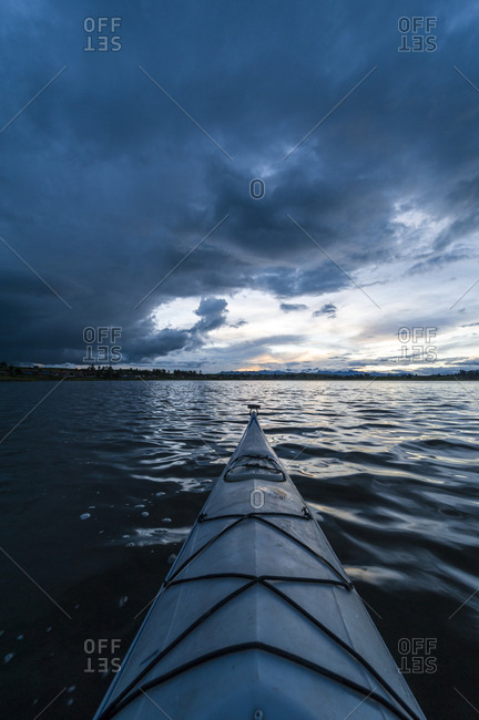 A canoe bow on a still lake in the Andes mountains beneath storm clouds.