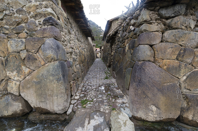 An irrigation canal in a village lane paved with stones and lined with high Inca dry-stone walls.