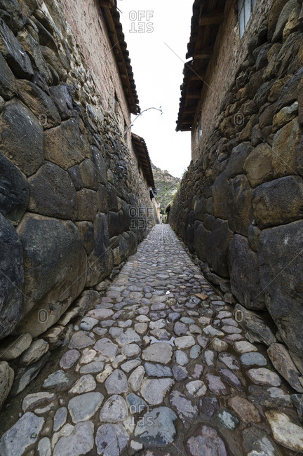 A village lane paved with stones and lined with high Inca dry-stone walls.