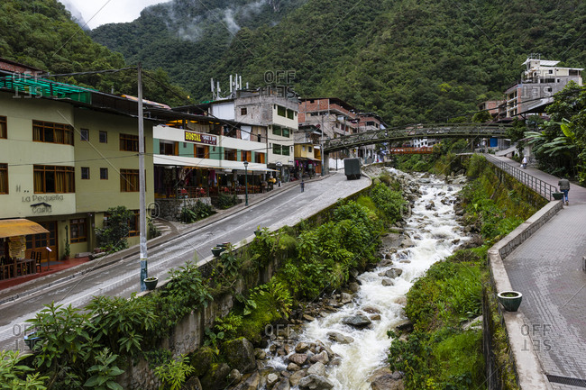 Peru - April 9, 2015: A river running through a town in a valley in the Andes mountains.