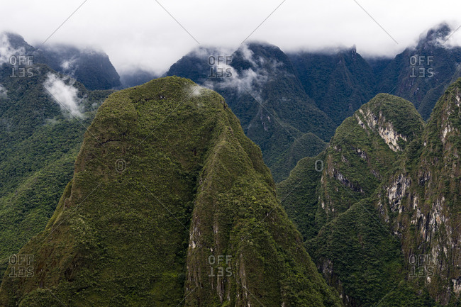 Sheer mountains covered in forest and jagged peaks above deep valleys in the Andes.