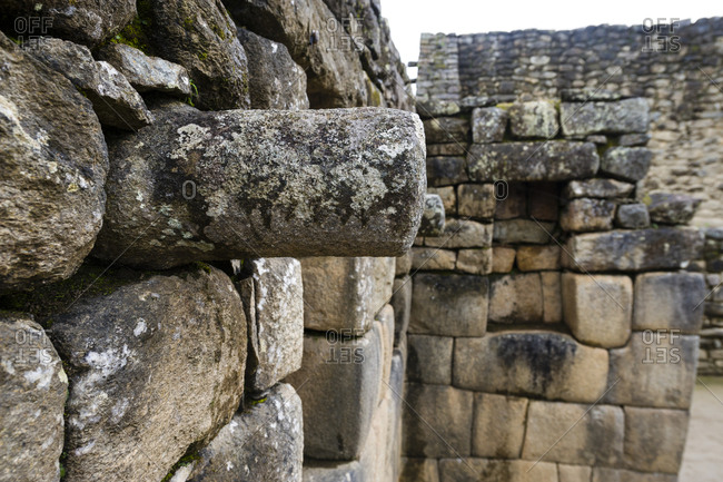 A stone joist emerges from a wall to support a ceiling in a Inca building.