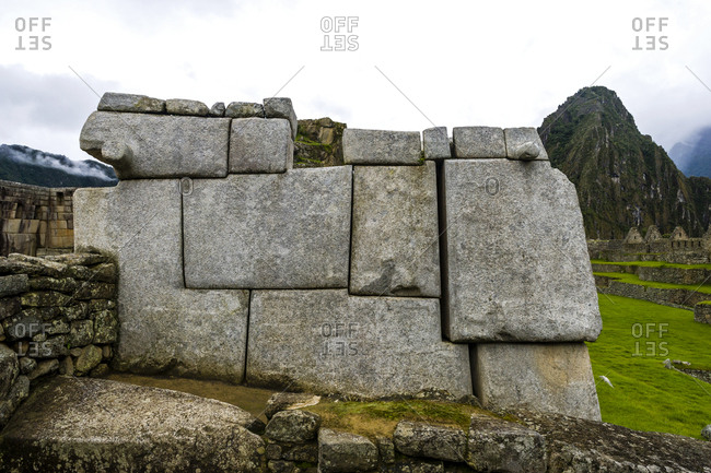 Large rocks shaped to fit a geometric Inca dry-stone wall in the ruins at Macchu Picchu.