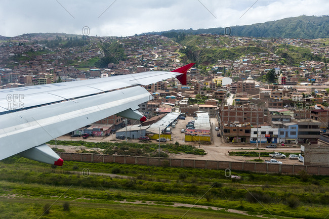 Cusco, Peru - April 19, 2015: A plane wing flying over an airport and city suburbs in the Andes mountains.