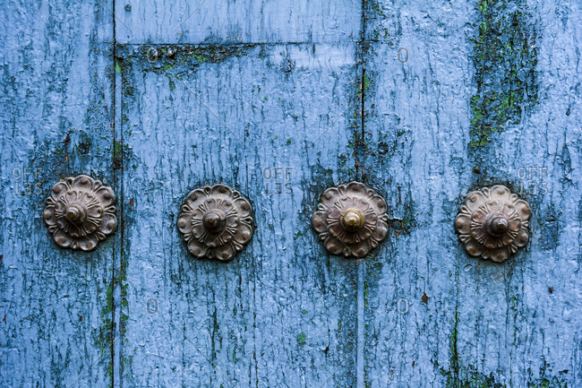 Steel studs in a weathered blue timber door in the Andes mountains.