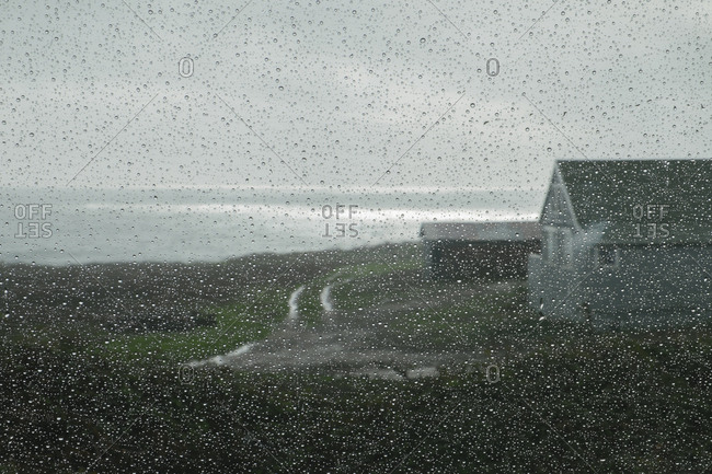 A farm and seascape seen though a car windshield in the rain.