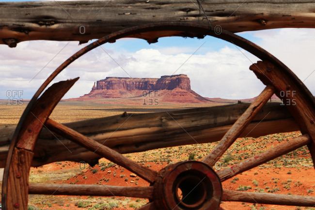 An old wagon wheel frames distant Sentinel Mesa.