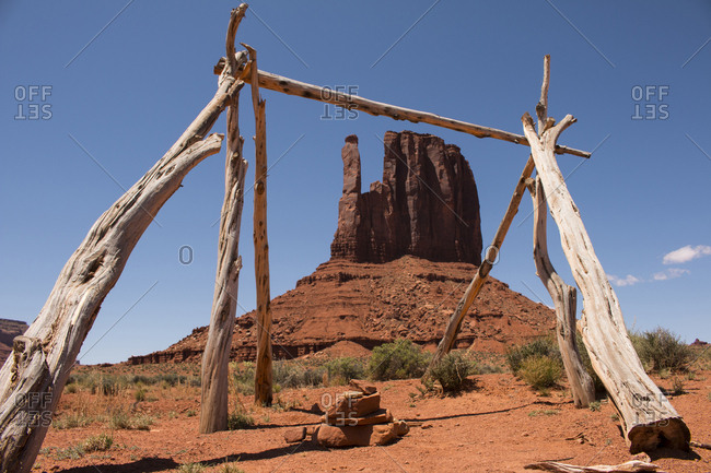 The cedar framework of a Navajo Tribe sacred site frames the West Mitten Butte in Monument Valley.