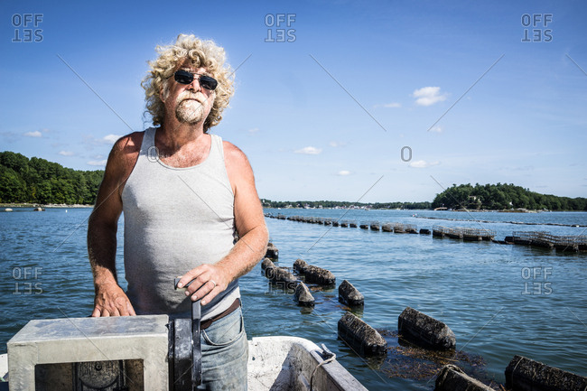 An oyster fisherman drives a boat down the river along his oyster beds.