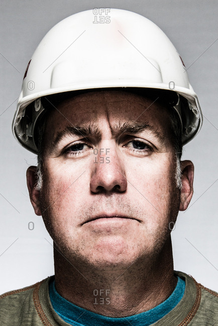 Portrait of a man wearing a hard hat and green shirt.
