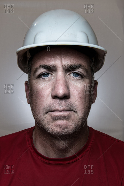 Portrait of a man wearing a hard hat and red shirt.