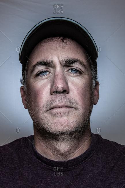 Portrait of a man wearing a baseball cap.