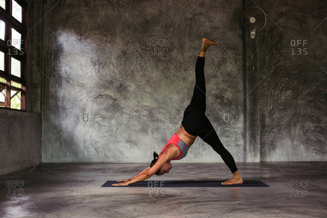 Woman bending forward in a yoga pose with her leg in the air