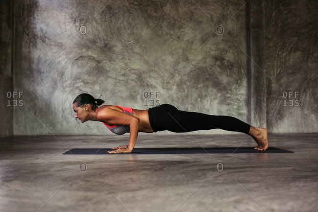 Woman in a yoga plank pose with her arms bent