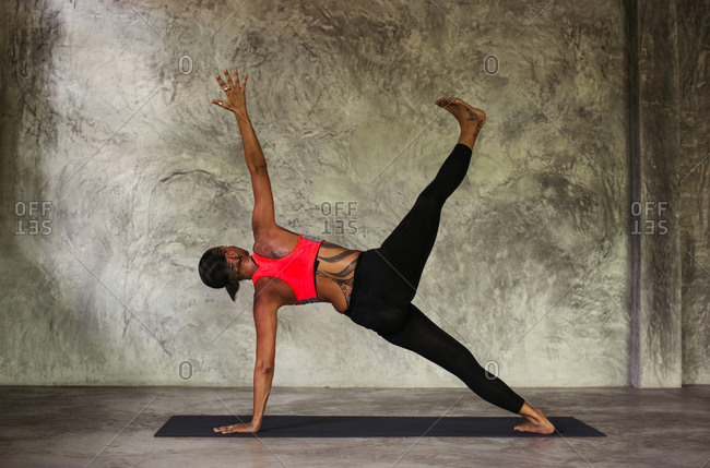 Woman in a side plank yoga pose with one leg lifted