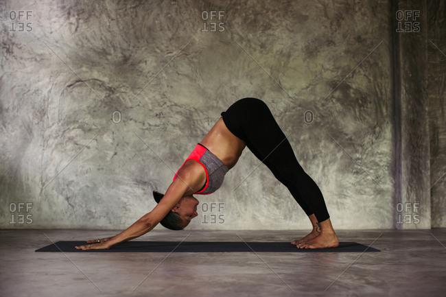 Woman practicing a downward facing dog yoga pose