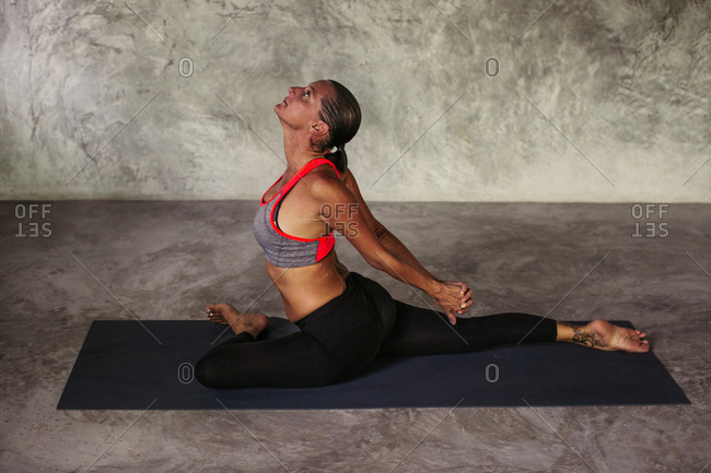 Woman practicing a pigeon yoga pose with her arms clasped behind her